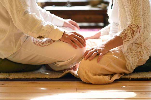 As mãos de um homem e uma mulher frente a frente em postura de lótus, meditando, conceito.
