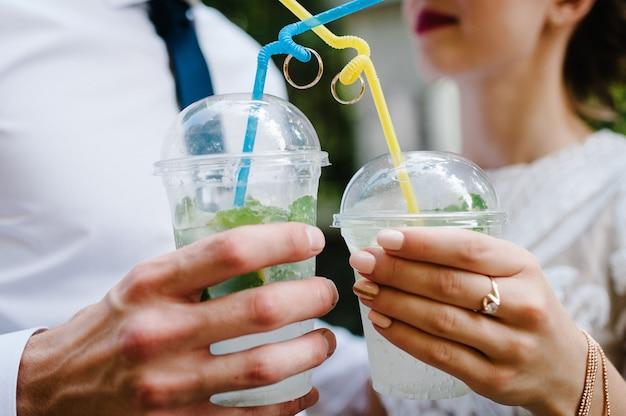 As mãos de um homem e uma mulher seguram copos de plástico com vinho
