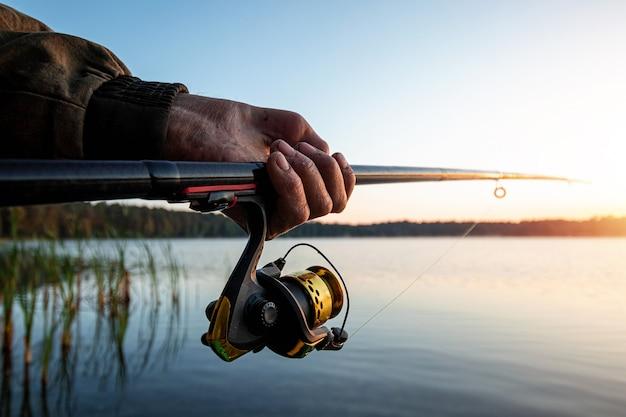 As mãos de um homem em um plano de urp seguram uma vara de pescar, um pescador pega peixe ao amanhecer