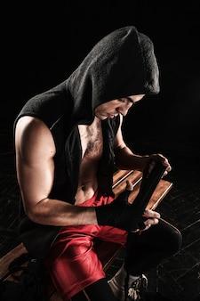 As mãos de um homem musculoso com bandagem