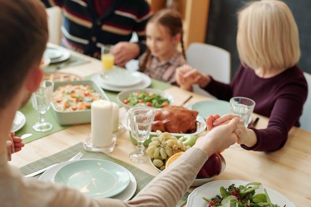 As mãos de um jovem, de uma mulher loira madura e do resto da família abraçados à mesa festiva durante a oração de ação de graças