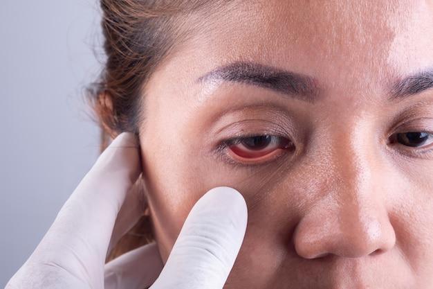 As mãos de um oftalmologista e um jovem paciente asiático. visitando a saúde ocular