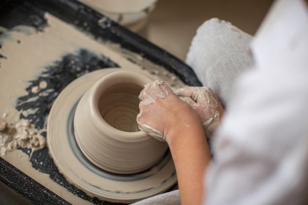 As mãos de um profissional que cria uma panela de barro na roda de oleiro. close-up, vista superior. oficina de cerâmica, processo de trabalho.