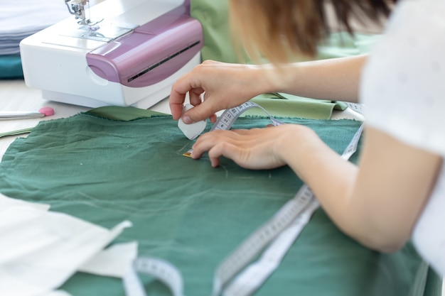 As mãos de uma jovem designer fazem marcas para um novo produto de costura, sentado à mesa ao lado da máquina de costura. conceito de design e negócios criativos.