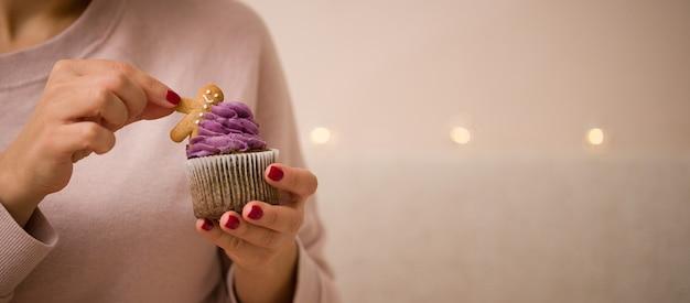 As mãos de uma jovem seguram um bolo de natal delicioso e doce decorado com um boneco de pão de gengibre
