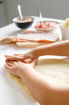 As mãos de uma menina preparando uma massa de pizza para colocar os ingredientes