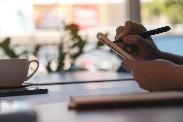 As mãos de uma mulher escrevendo em um caderno e trabalhando em dados de negócios e documentos sobre a mesa no escritório