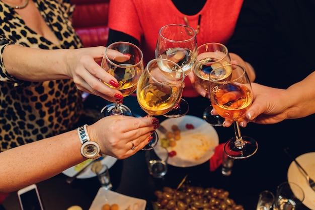 As mãos de uma mulher idosa com uma taça de vinho pegando outra taça de vinho.