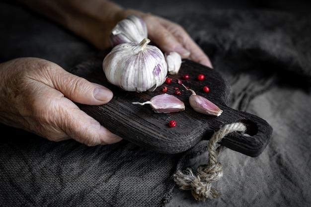 As mãos de uma mulher idosa seguram uma tábua de cortar com alho em um fundo cinza têxtil
