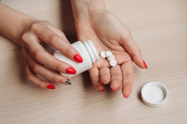 As mãos de uma mulher, nas mãos de uma grande pílula branca e redonda em suas mãos. medicamentos vitamínicos