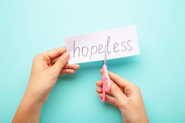As mãos de uma mulher seguram um papel com a palavra hopeless, corte-o com uma tesoura para fazer hope