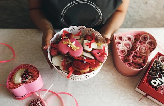 As mãos de uma mulher seguram um vaso de biscoitos coloridos em forma de coração