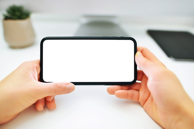 As mãos de uma mulher segurando e usando um telefone celular preto com tela em branco horizontalmente para assistir.