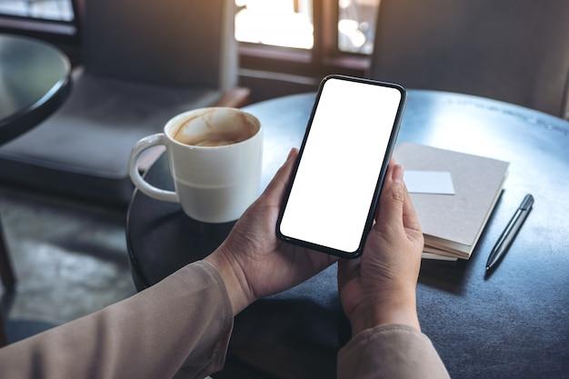 As mãos de uma mulher segurando e usando um telefone celular preto com tela em branco para assistir com o caderno e a xícara de café na mesa de madeira