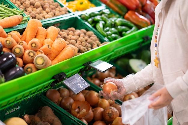 As mãos de uma mulher sênior com luvas protetoras, escolhendo cebolas no supermercado.