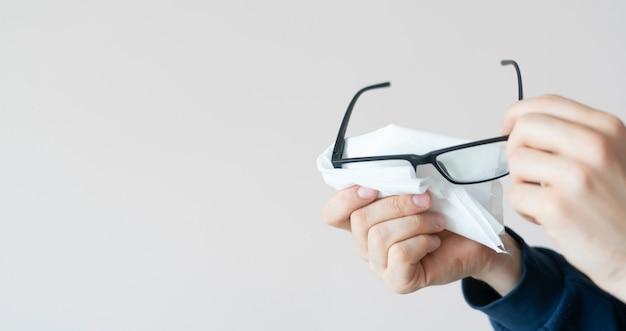 As mãos de uma pessoa segurando óculos e limpando as lentes, visão limpa