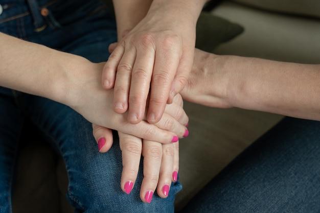 As mãos de uma senhora idosa tocam as mãos de uma jovem