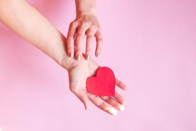 As mãos de uma senhora segurando um coração sobre a superfície,