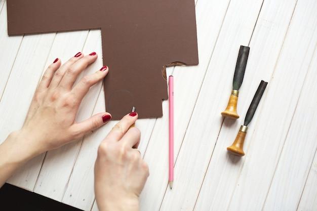 As mãos desenham e esculpem uma linogravura, conceito de artesanato