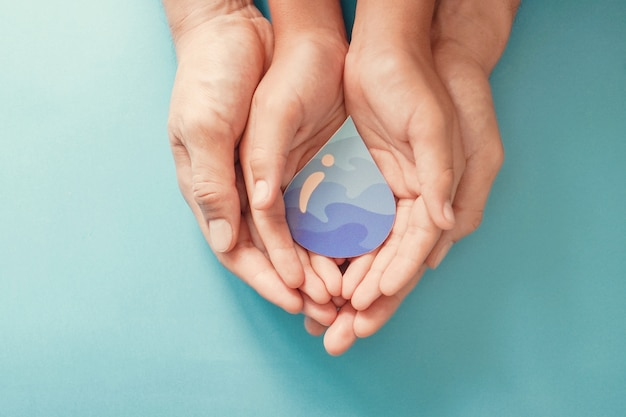 As mãos do adulto e da criança que guardam o papel cortam a gota da água. dia mundial da água. água limpa e saneamento, rse, economizam água.