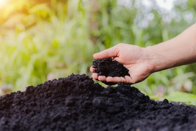 As mãos do agricultor aram o solo para se preparar para o plantio.