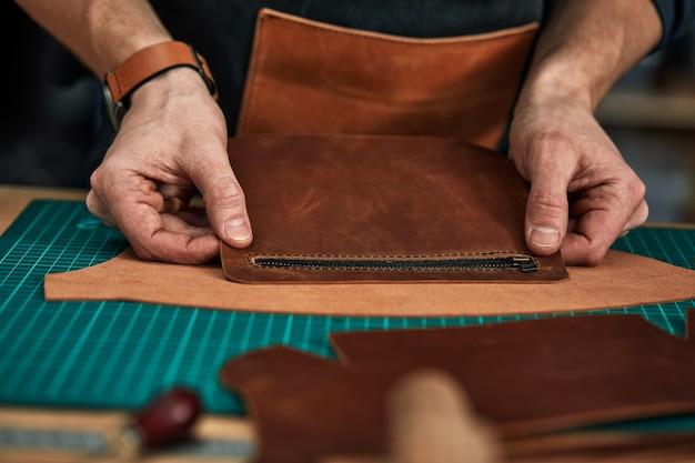 As mãos do alfaiate estão experimentando um detalhe de um produto de couro, uma sauna a vapor de couro coleta um produto de couro dos detalhes, alfaiataria.