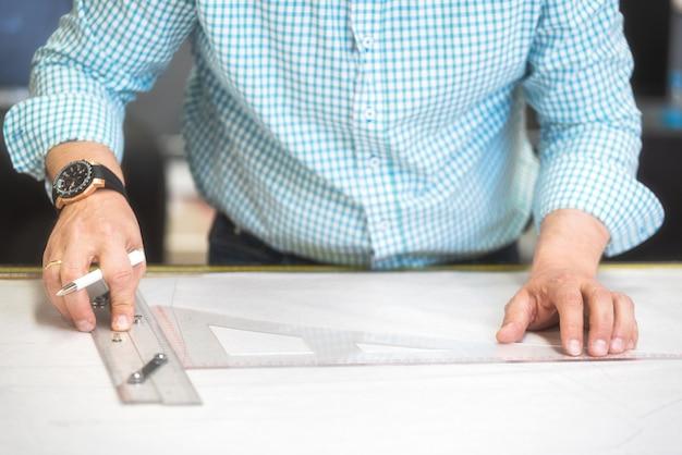 As mãos do alfaiate marcam o desenho no papel do ofício para fazer testes padrões.