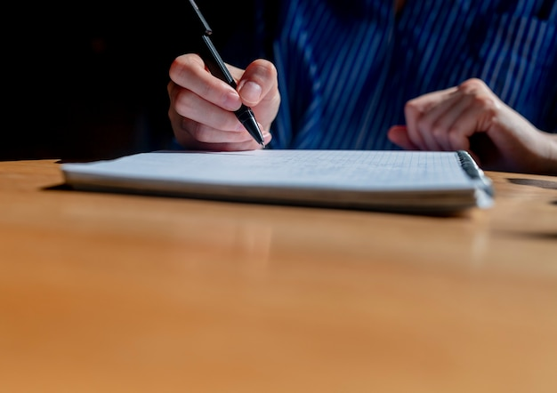 As mãos do aluno fecham escrevendo com uma caneta no bloco de notas ou planejador fazendo anotações na mesa de escritório de madeira com ...