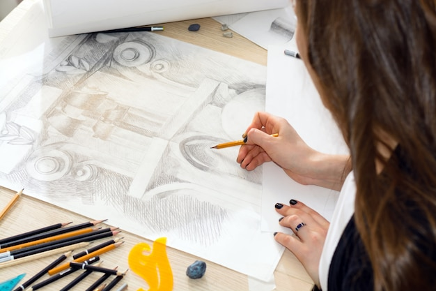 As mãos do arquiteto estudante com um lápis, preparando um padrão de luz e sombra, design closeup de balaústre em uma mesa de madeira