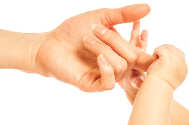 As mãos do bebê recém-nascido seguram os dedos da mãe no fundo branco