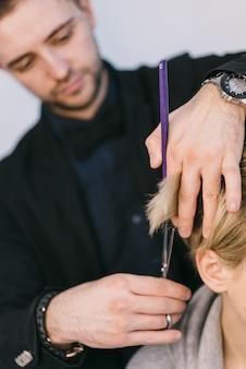 As mãos do cabeleireiro cortam o cabelo do louro com o uso de tesouras em um estúdio da beleza. fechar-se