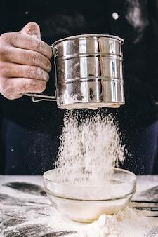 As mãos do chef estão jogando farinha sobre uma mesa de madeira