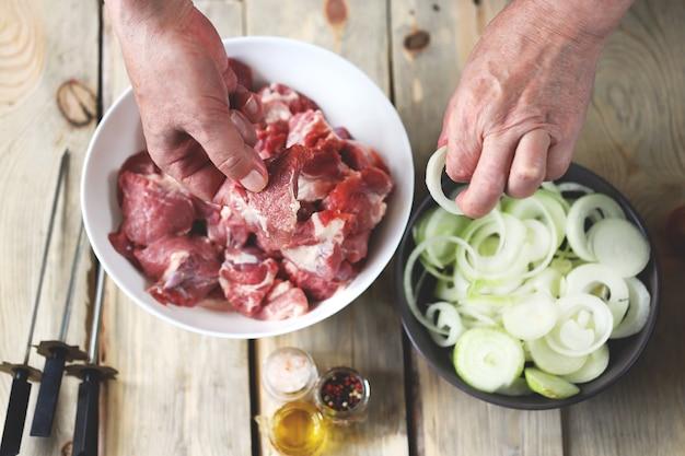 As mãos do chef estão preparando o espetinho de carne com cebola. uma tigela de carne crua e uma tigela de cebolas. cozinhar churrasco.