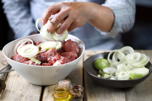 As mãos do chef estão preparando o espetinho de carne com cebola.