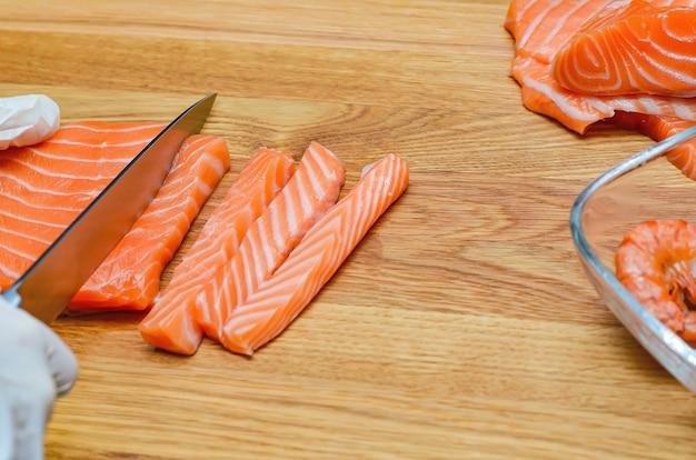 As mãos do chef fecham. em uma tábua de madeira, o chef corta um peixe vermelho com uma faca. salmão para sushi japonês