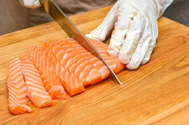 As mãos do chef fecham. em uma tábua de madeira, o chef corta um peixe vermelho com uma faca.