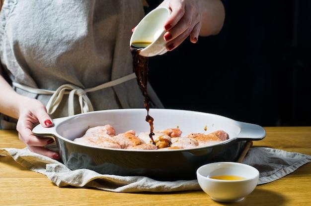 As mãos do chef marinam as asas de frango cru.