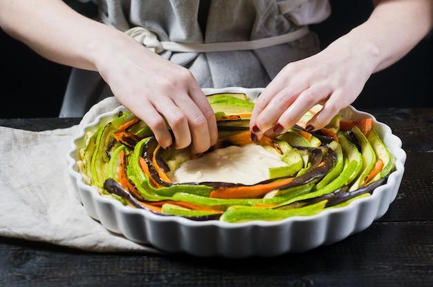As mãos do chef preparam ratatouille em uma assadeira.