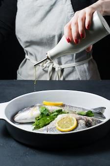 As mãos do chef regaram o peixe dorado com azeite.
