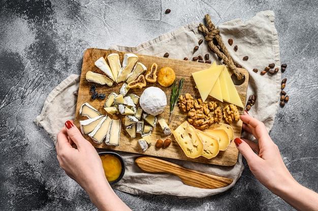 As mãos do chef segurando uma bandeja de queijo serviram com nozes e figos. fundo cinza. vista do topo