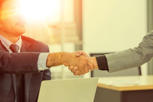 As mãos do close up apertam o sucesso da parceria de negócios, conceito de aperto de mão