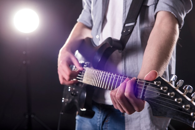 As mãos do close-up do homem novo estão jogando a guitarra.