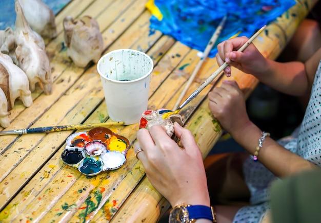 As mãos do close up dos estudantes de arte que guardam a escova de pintura estudam e que aprendem a pintura na boneca animal de madeira na sala de aula de arte.