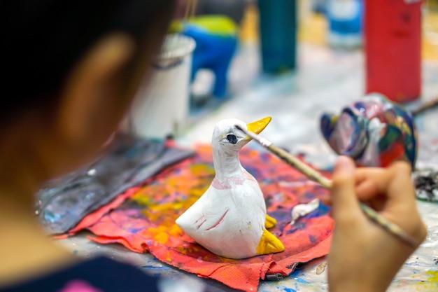 As mãos do close up e da colheita da menina que guardam a escova de pintura estudam e que aprendem a pintura na boneca animal de madeira na sala de aula de arte de sua escola.