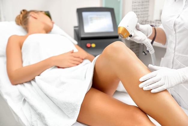 As mãos do cosmetologista fazem a depilação das pernas