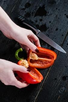 As mãos do cozinheiro chefe cortaram a pimenta de sino vermelha na tabela de madeira preta.