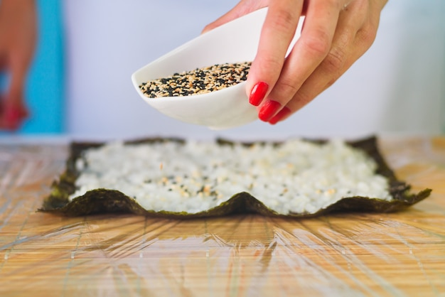 As mãos do cozinheiro chefe da mulher que enchem rolos de sushi japoneses com arroz e sésamo em uma folha de alga do nori.