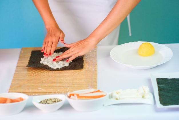 As mãos do cozinheiro chefe da mulher que enchem rolos de sushi japoneses com arroz em uma folha de alga do nori.