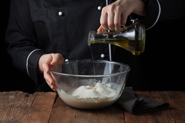 As mãos do cozinheiro chefe derramam o azeite na bacia na massa crua.