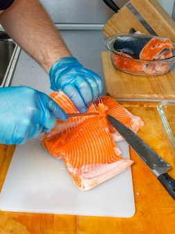 As mãos do cozinheiro separam os filés de salmão dos ossos com uma faca